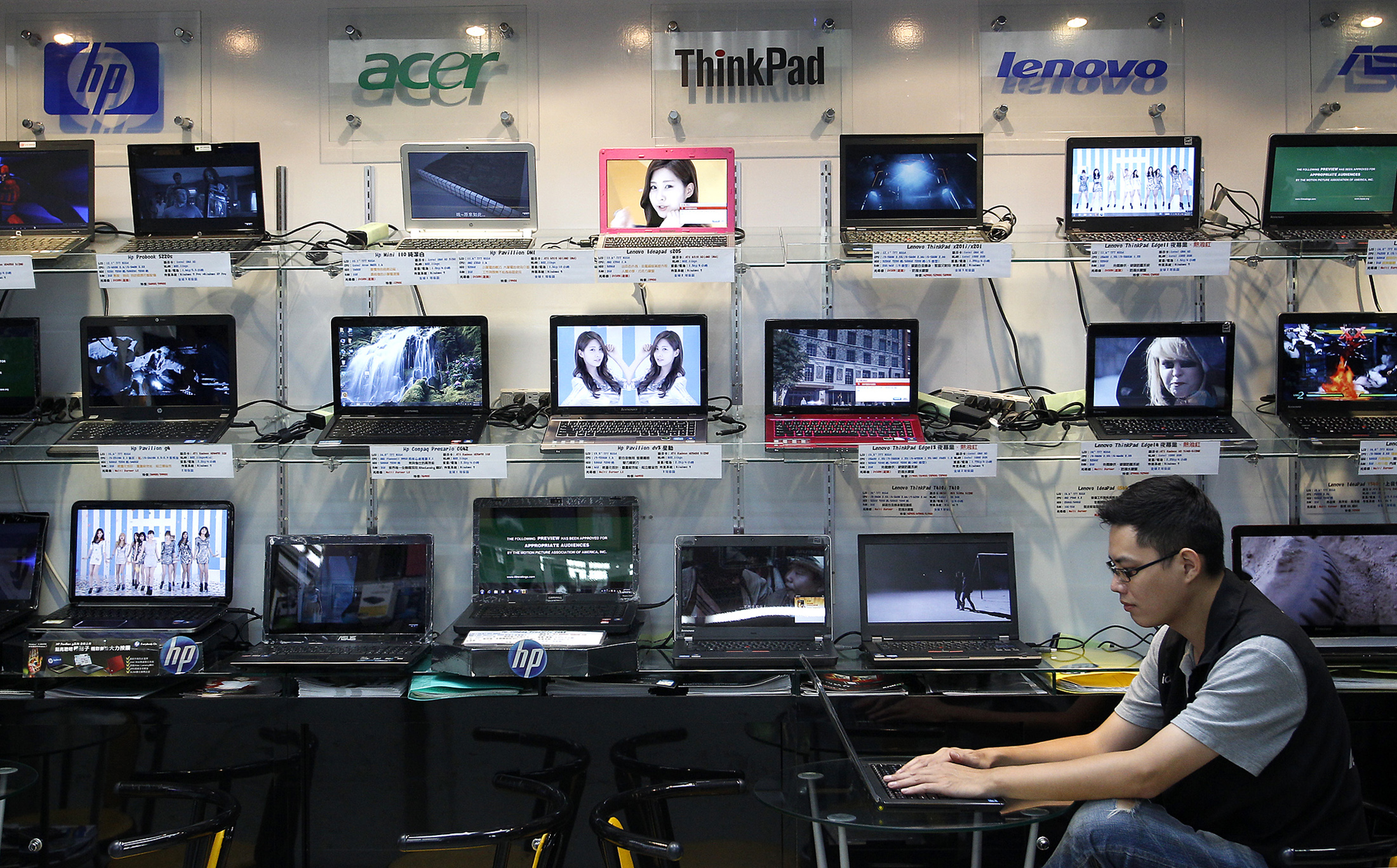 A shop attendant sits in front of a wall of laptops at a computer mall in Taipei August 31, 2011. The world's top two contract laptop makers gave subdued outlooks for this year in the face of stiff competition from tablet PCs and a deep malaise in major western economies that is sapping consumer buying power. REUTERS/Pichi Chuang (TAIWAN - Tags: BUSINESS SCIENCE TECHNOLOGY) - RTR2QKGR